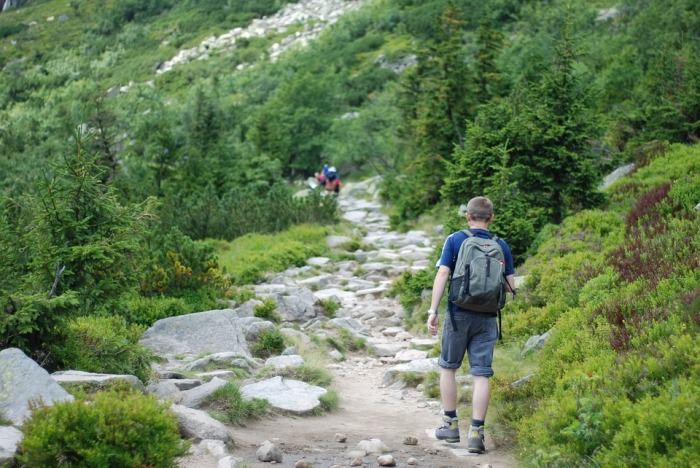 young male wearing a backpack walking up a rocky trail in the woods