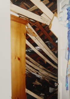 boards hanging from the roof inside a house destroyed by hurricane katrina