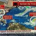 photo of a television screen showing a weather map with hurricanes Harvey and Irma