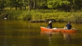 canoe with man and woman in lake or slow moving river