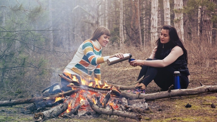 2 women sitting beside a campfire sharing a drink from a thermos